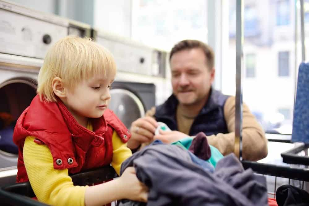 A little boy loads clothes into the washing machine in public laundromat