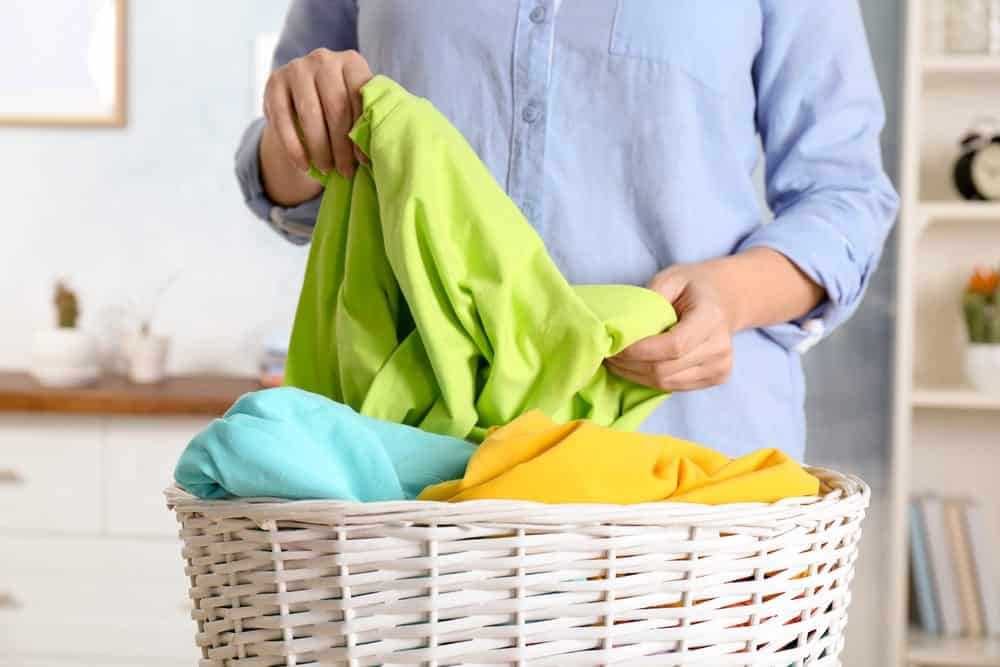 Close-up of woman sorting brightly colored laundry in basket