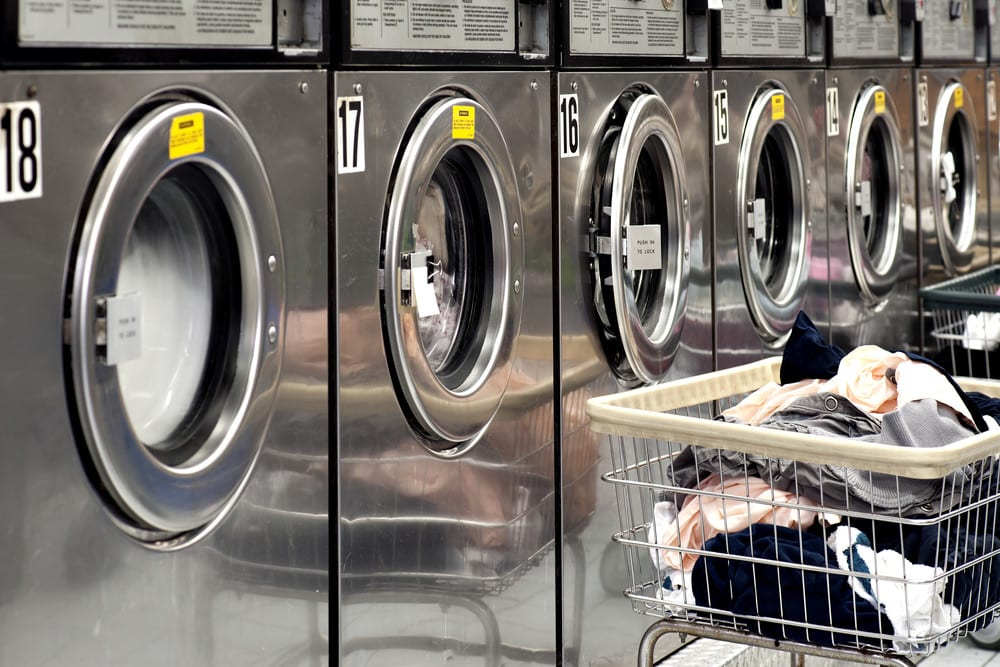 A row of industrial washing machines in a public laundromat, with laundry in a basket