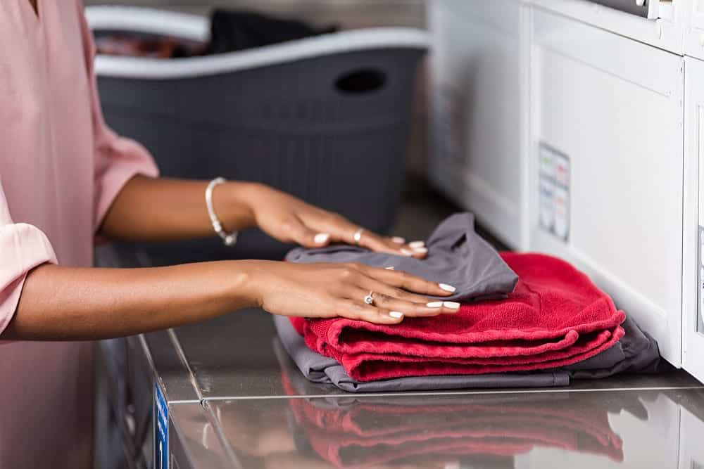 Close-up of young woman folding clothes in a laundromat