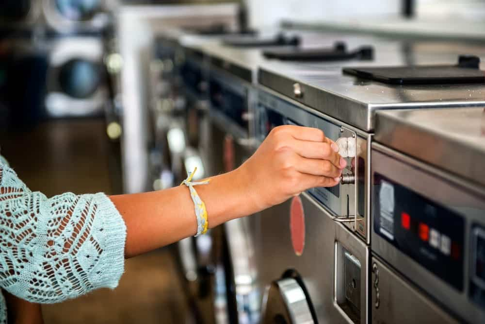 Close-up of hand inserting coin into laundry machine at laundromat