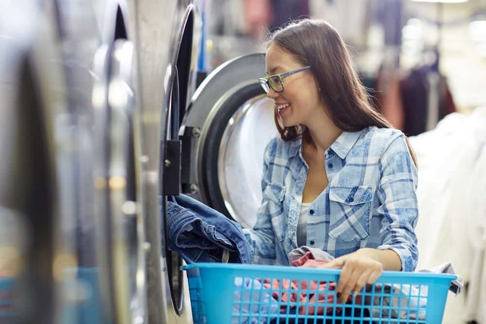Young woman putting clothes into washing machine at laundromat