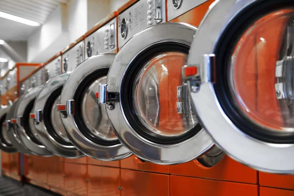 Line of Orange Washing Machines with Doors Open in a Laundromat