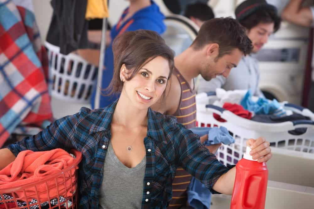 Smiling woman in a busy laundromat