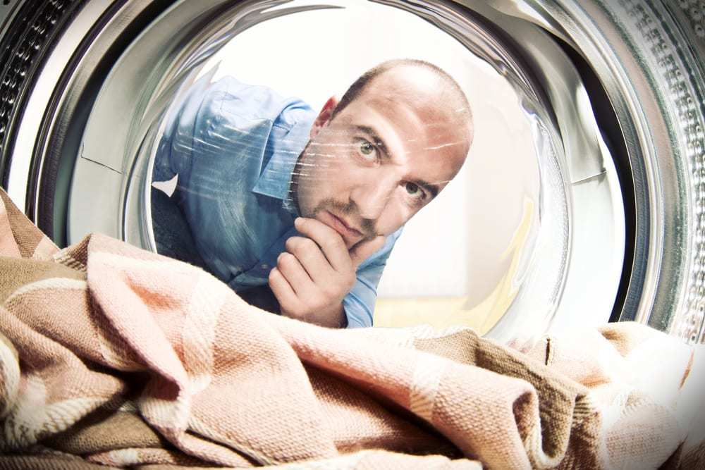 Shot from inside the dryer, man looking inside at dry towels with uncertain expression