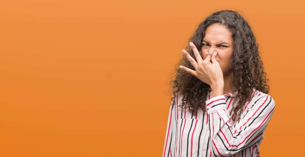 Woman holding nose at stinky odor, orange background