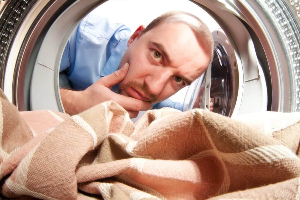 Man Looking Inside Washing Machine with Quizzical Expression