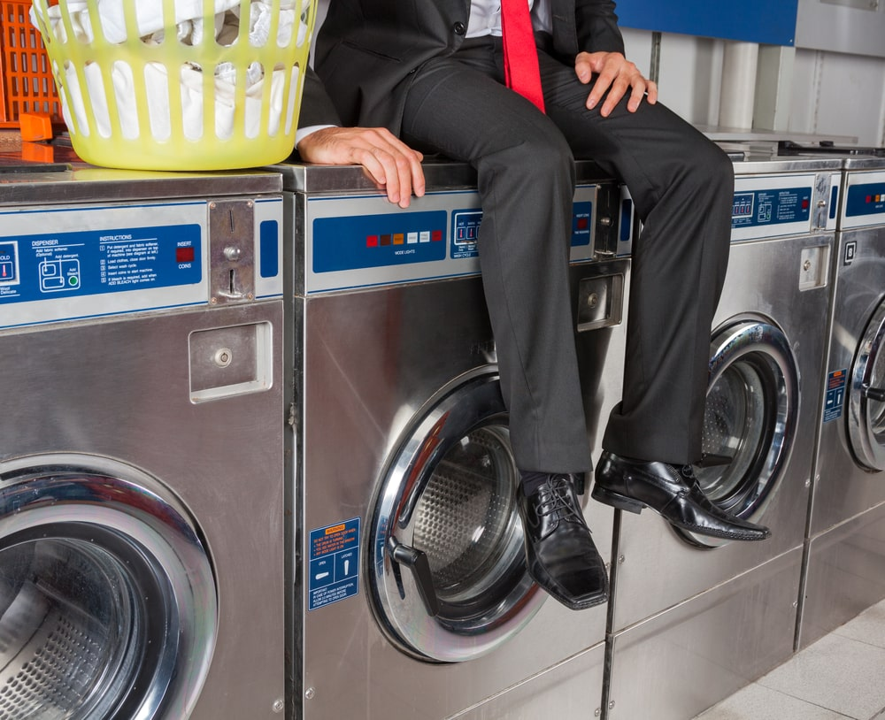 Man in business suit sitting on washing machine in laundromat