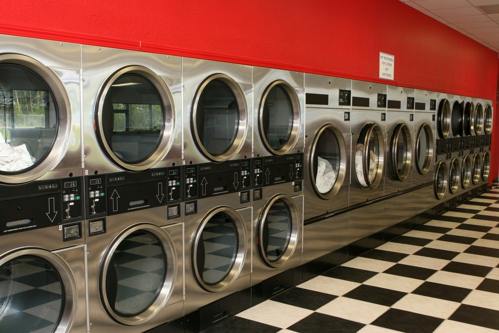 Row of dryers in a clean, bright laundromat