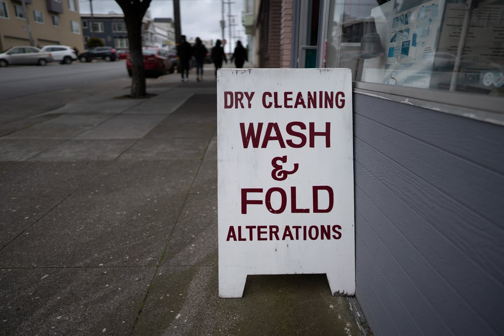 """sign outside shop reading """"dry cleaning, wash & fold, alterations"""""""