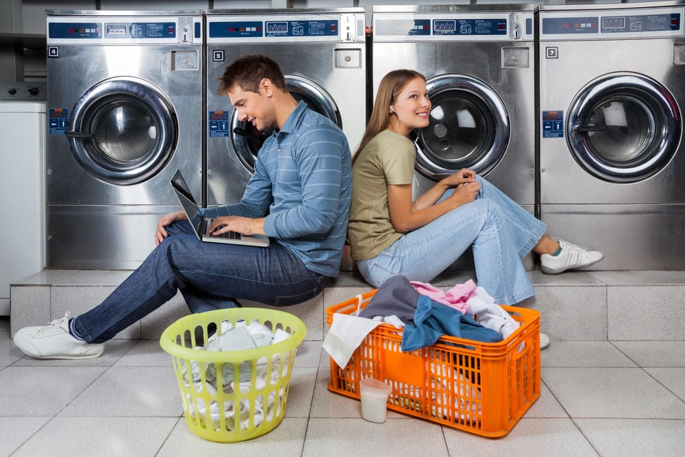 Young couple sitting in laundromat using laptop and earbuds